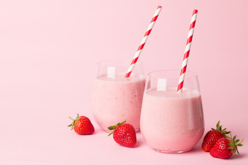A glass of fresh strawberry smoothie on a pink background. Summer drink shake, milkshake and refreshment organic concept.