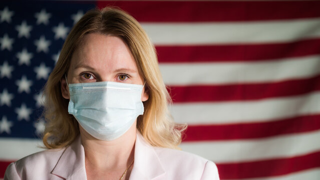 Portrait of a woman of a businessman in a protective mask against the background of the U.S. flag