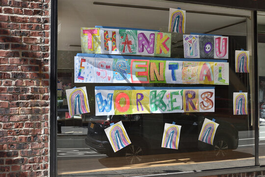 """Colorful hand-drawn letters on a glass window spelling out """"Thank you essential workers"""", May 31, 2020, in New York."""
