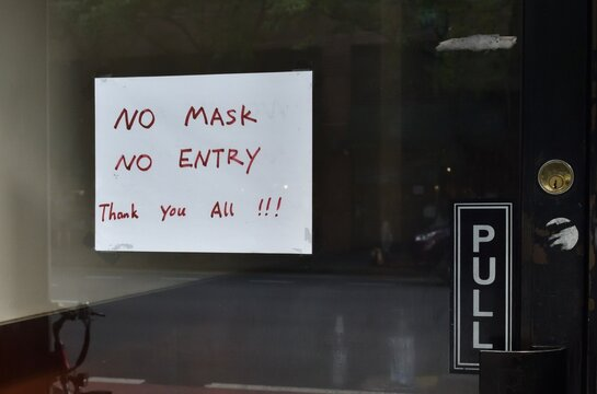 """Handwritten sign on a glass shop door reading """"No mask no entry thank you all!!!"""", May 30, 2020, in New York."""