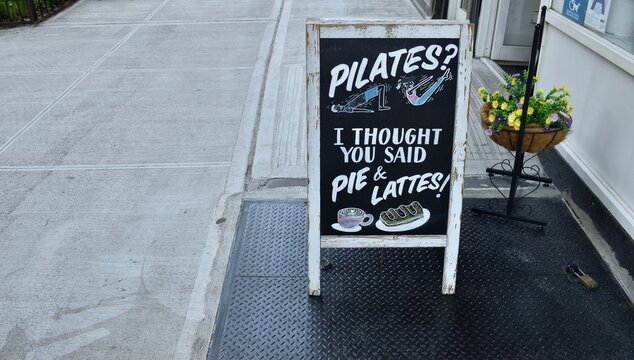 """A-frame blackboard sign reading """"Pilates? I thought you said pie and lattes!"""" on a city sidewalk outside a coffee shop, May 14, 2020, in New York."""