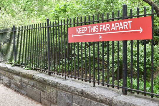 """Sign on a black metal park fence reading """"Keep this far apart"""", May 8, 2020, in New York."""