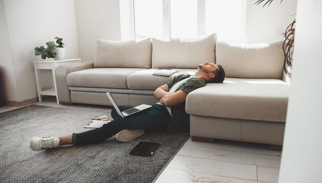 Tired caucasian man falling asleep on the floor with a computer and tablet with crossed hands
