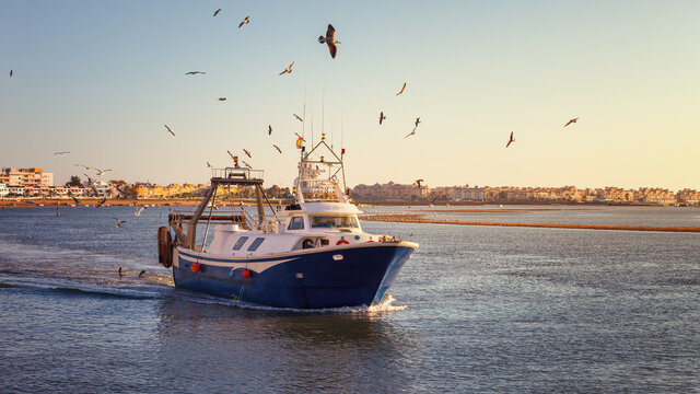 Fishing boat at sunset arriving at the port of Isla Cristina, after a long day at work in the waters of the Atlantic Ocean, Spain