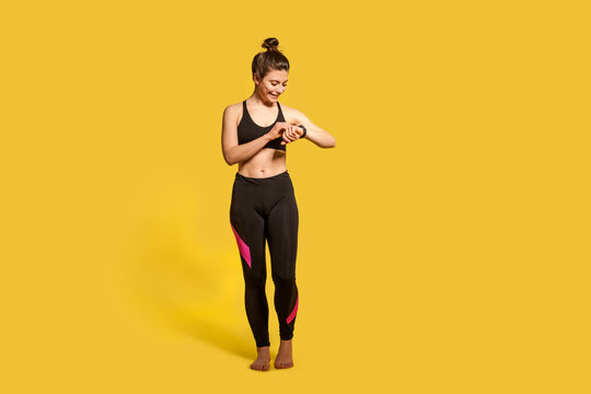 Cheerful athletic woman with hair bun in tight sportswear touching wristwatch display, checking pulse time on fitness tracker, smiling satisfied with health indicators after trainings. Sport activity