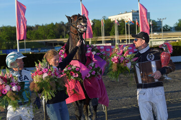 Driver Orjan Kihlstrom, trainer Daniel Reden and horse Propulsion celebrate after the final of Elitloppet trotting event at Solvalla track without an audience due to the coronavirus disease (COVID-19) outbreak, in Stockholm