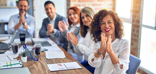 Group of business workers smiling happy and confident. Working together with smile on face looking at the camera applauding at the office Fotobehang