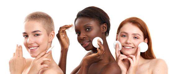 Skin care for everyone. Three positive multicultural young women removing makeup from face with cotton pads and smiling while standing in studio against white background