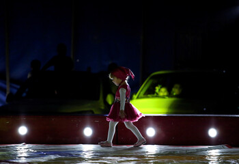 A girl artist walks on stage during a circus performance in Atayde's Circus tent, where people enjoy the show from their cars as a measure to combat the spread of the coronavirus disease (COVID-19), in San Nicolas de los Garza