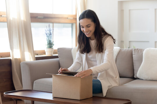 Smiling millennial girl unpack cardboard postal box with order shopping online, happy young woman unbox post carton package, make purchase buy on internet web, good delivery service concept