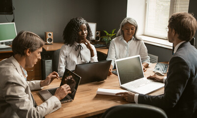 Brainstorming of Diverse group employees working together on a new business project. Young African girl, an elderly gray-haired Asian woman and two Caucasian young men share their ideas.