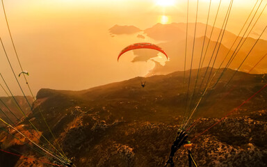 Extreme sport. Landscape .Paragliding in the sky. Paraglider tandem flying over the sea with blue water and mountains in bright sunny day. Aerial view of paraglider and Blue Lagoon in Oludeniz, Turkey