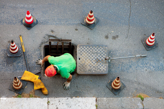 sequence of worker going in the manhole in the street, step 3