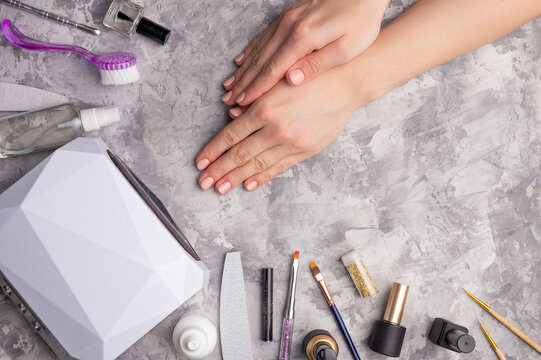 Gel polishes and nail care. Girl does manicure at home. Work at home. Hands of a young girl with painted nails, and tools for working with nails. On a gray concrete background.