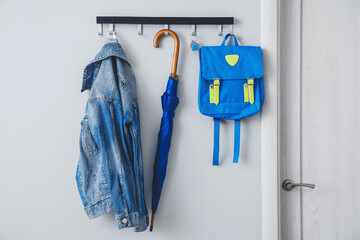 Umbrella with clothes and school backpack hanging on wall in hall