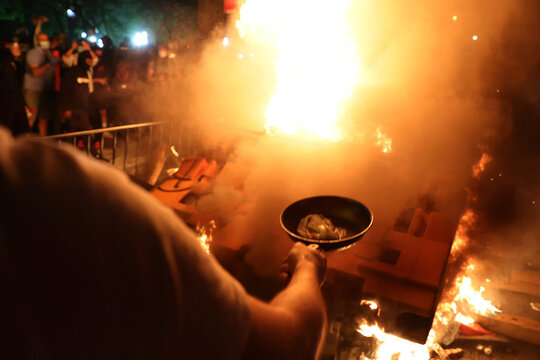 A protester fries bacon in a pan over a bonfire in the midst of protests against the death in Minneapolis police custody of George Floyd near the White House in Washington