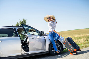 Fototapeta Pretty girl with suitcase standing near car and wiat for her dreaming trip. obraz