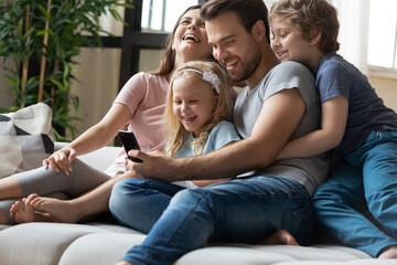 Keuken foto achterwand Texturen Happy young family with little children relax on sofa at home laugh watch funny video on smartphone together, smiling parents with small preschooler kids rest on couch have fun using modern cellphone