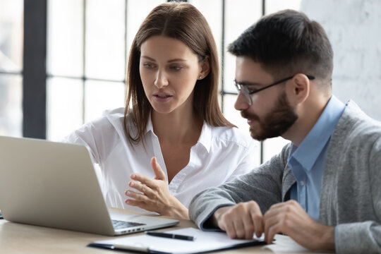 Confident businesswoman pointing at laptop screen, training new employee, helping with corporate software, serious mentor coach teaching worker, colleagues discussing online project, working together