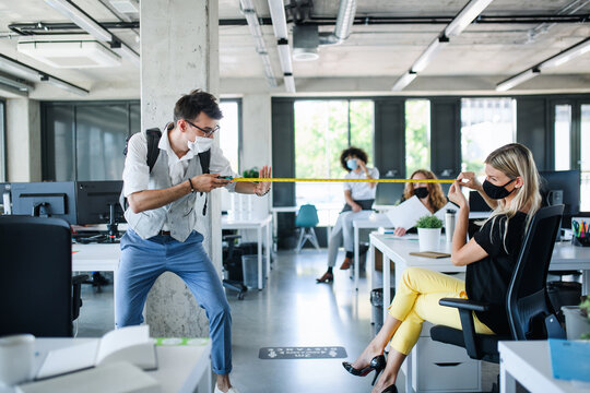 Young people with face masks back at work in office after lockdown, measuring distance.