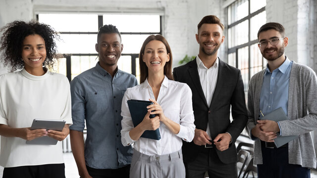 Corporate portrait successful smiling diverse employees team standing in office, posing for photo with confident businesswoman team leader executive, looking at camera, unity and cooperation