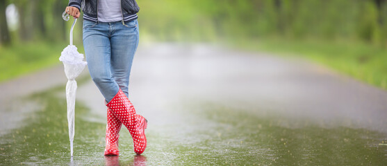 Detail of female legs in rain boots and a closed umbrella standing on the road on a rainy day Fotobehang