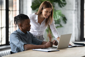 Smiling businesswoman mentor helping new African American employee with corporate software, training and teaching, standing near desk, looking at screen, supervisor checking intern work results