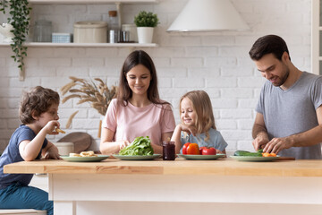 Happy young Caucasian family with small children preparing breakfast in modern renovated kitchen together, smiling parents with little kids have fun cooking healthy eco food salad at home
