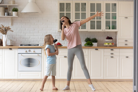 Funny young mom or nanny play sing entertain using kitchen appliances with little preschooler girl child, smiling overjoyed mother have fun enjoy family leisure weekend with small daughter at home