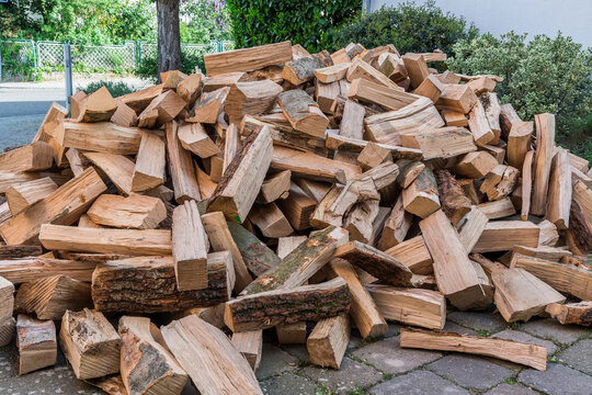 Messy pile of firewood on a drive, delivered for the winter stock