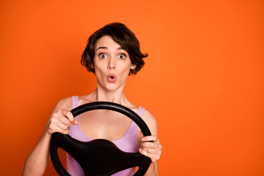 Portrait of astonished girl hold steering wheel ride drive car taxi impressed fast speed road wear good look singlet isolated over shine color background