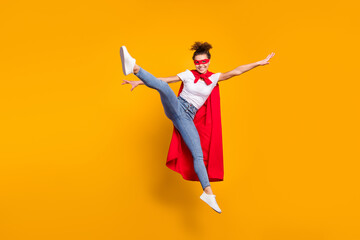 Full length body size view of her she nice attractive lovely energetic fit slim thin cheerful girl jumping wearing cape having fun isolated bright vivid shine vibrant yellow color background