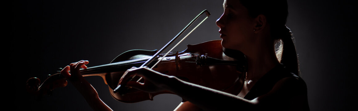 silhouette of female musician playing on violin on dark stage, panoramic orientation