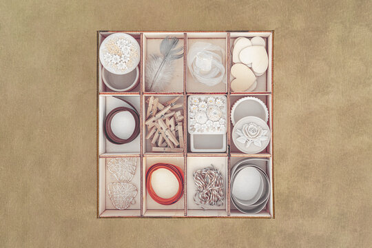 Wooden box with 12 compartments full of things shot against textured background