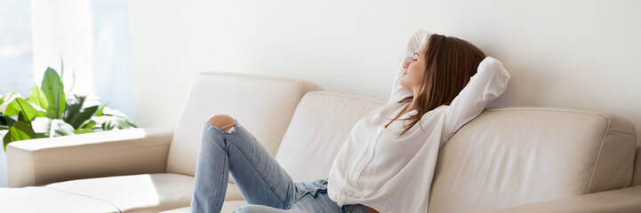 Beautiful woman in casual clothes resting leaned on leather sofa breath fresh air looks in distance enjoy weekend, modern apartment, vacation concept. Horizontal photo banner for website header design