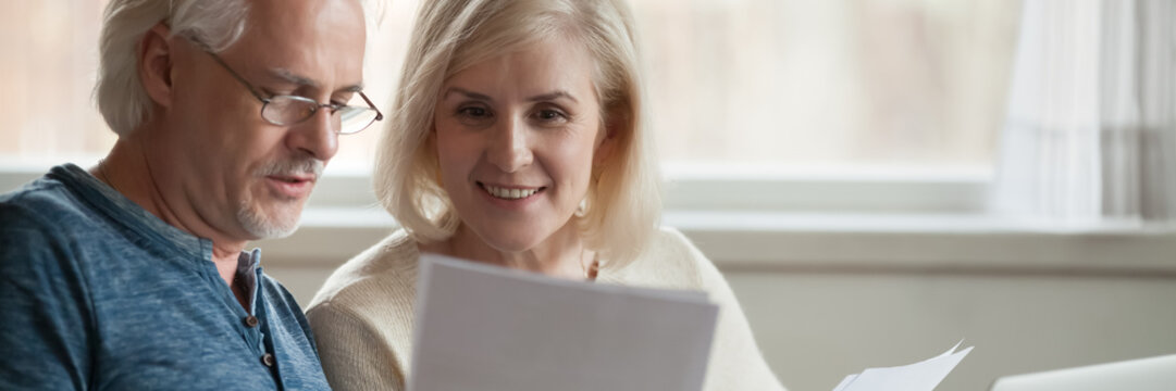 Elderly spouses read paper from bank, analyzing financial statement manage together family budget feels satisfied, enough money, taxes refund concept. Horizontal photo banner for website header design