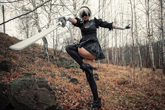 cosplay beautiful woman in the forest with black dress and with sword