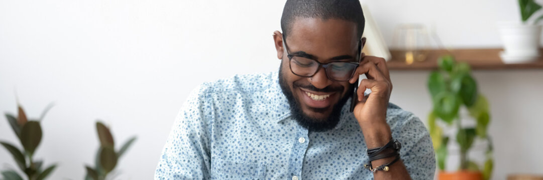 African millennial man holding smartphone enjoy distant conversation seated indoors, horizontal photo banner for website header design. Successful businessman make business call, informal talk concept