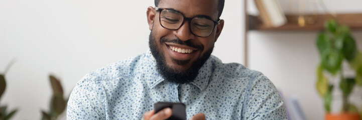 Smiling African businessman sit at workplace holding mobile phone, texting sms, browsing internet. Distant communication, virtual chat usage concept. Horizontal photo banner for website header design