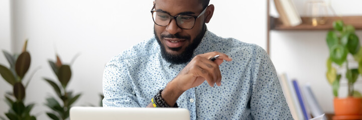 Millennial African employee sit at office desk using pc look at screen read e-mail, received good...