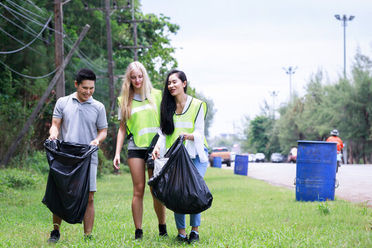 CSR activity. Corporate Social Responsibility. Three volunteers, Asian male, female and Caucasian are helping to pick up waste by garbage bags beside the road. Environmental problem. Environment day