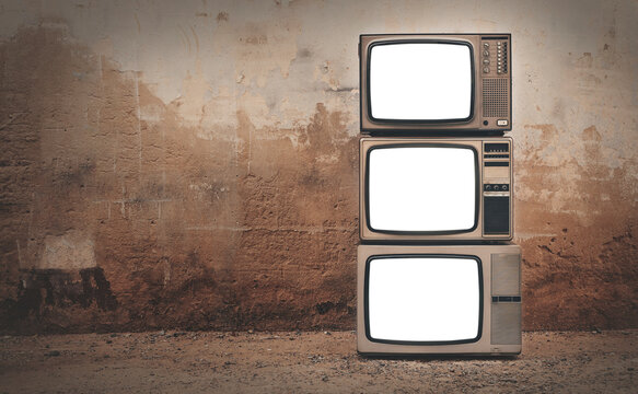 Retro old televisions cut out screen pile on floor in front of old wall background. Vintage style photo, Three old TVs with copy space on the left, clipping path