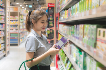Beautiful young asian woman shopping in a grocery supermarket.