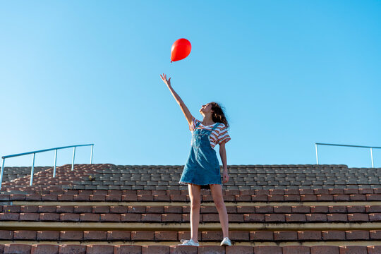 Young woman standing on granstand, letting go of a red ballon