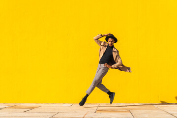 Young man dancing in front of yellow wall, jumping mid air