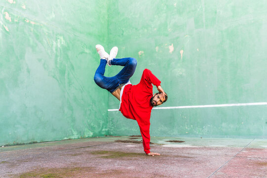 Portrait of bearded young man wearing red sweatshirt doung handstand on one hand