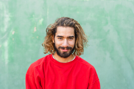 Portrait of bearded young man wearing red sweatshirt in front of green wall