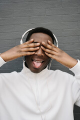 Portrait of young man listening music with headphones covering eyes while sticking out tongue