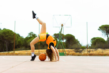 Teenage girl doing acrobatics on basketball ground