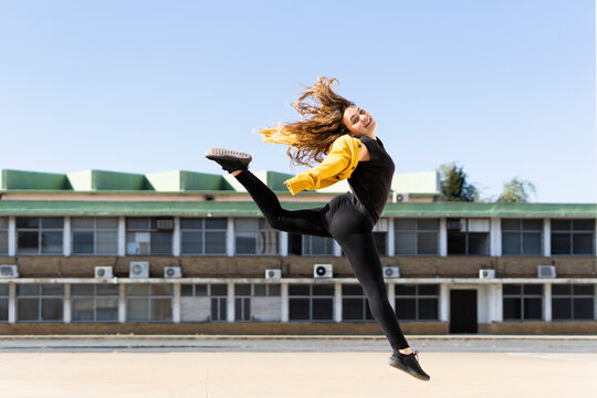 Happy teenage girl jumping outdoors
